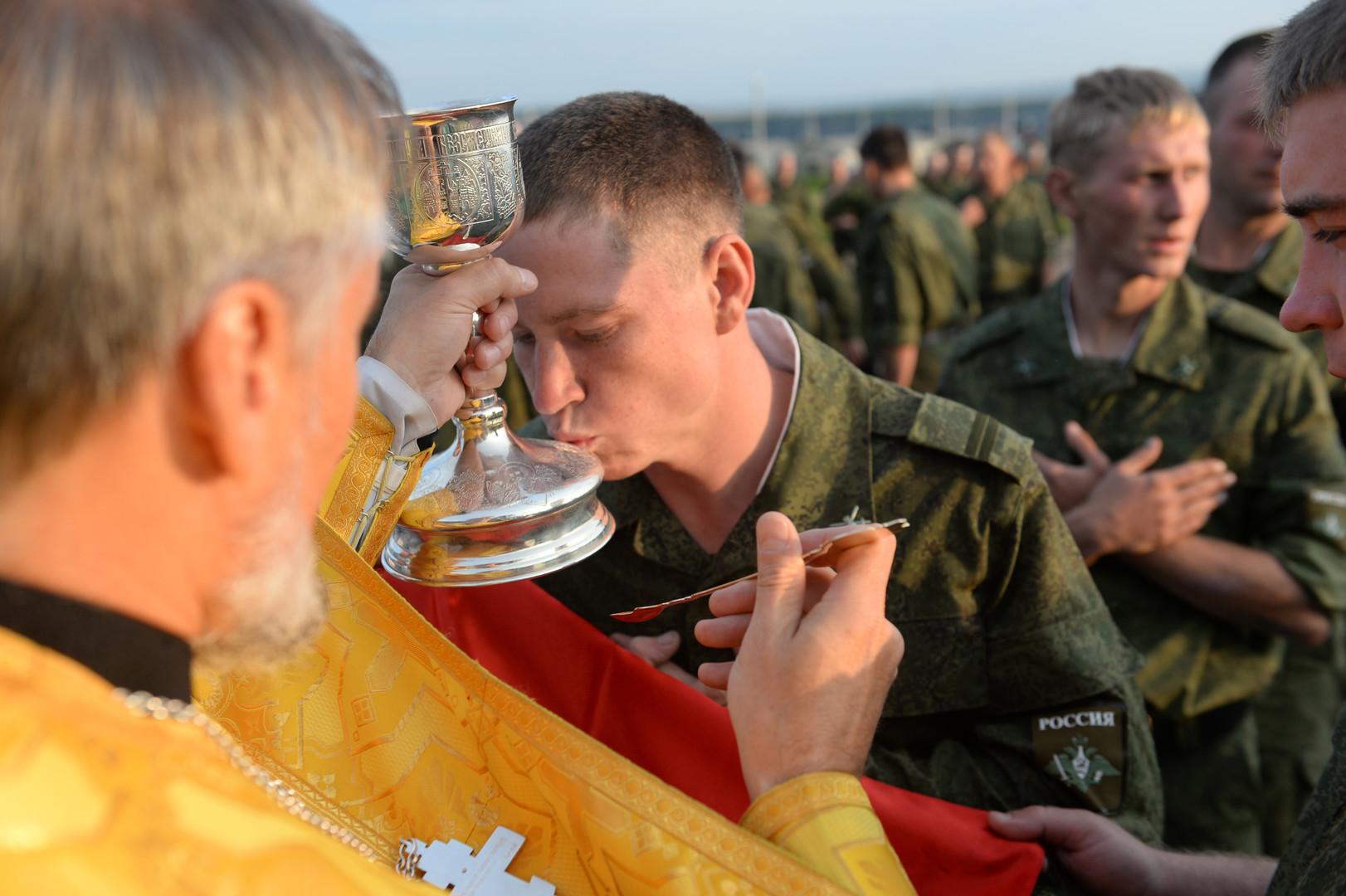 """Russische Armeeangehörige empfangen das Heilige Abendmahl  bei einer Messe während der russisch-chinesischen Anti-Terror-Übungen """"Friedensmission 2013"""" im Gebiet Tscheljabinsk."""