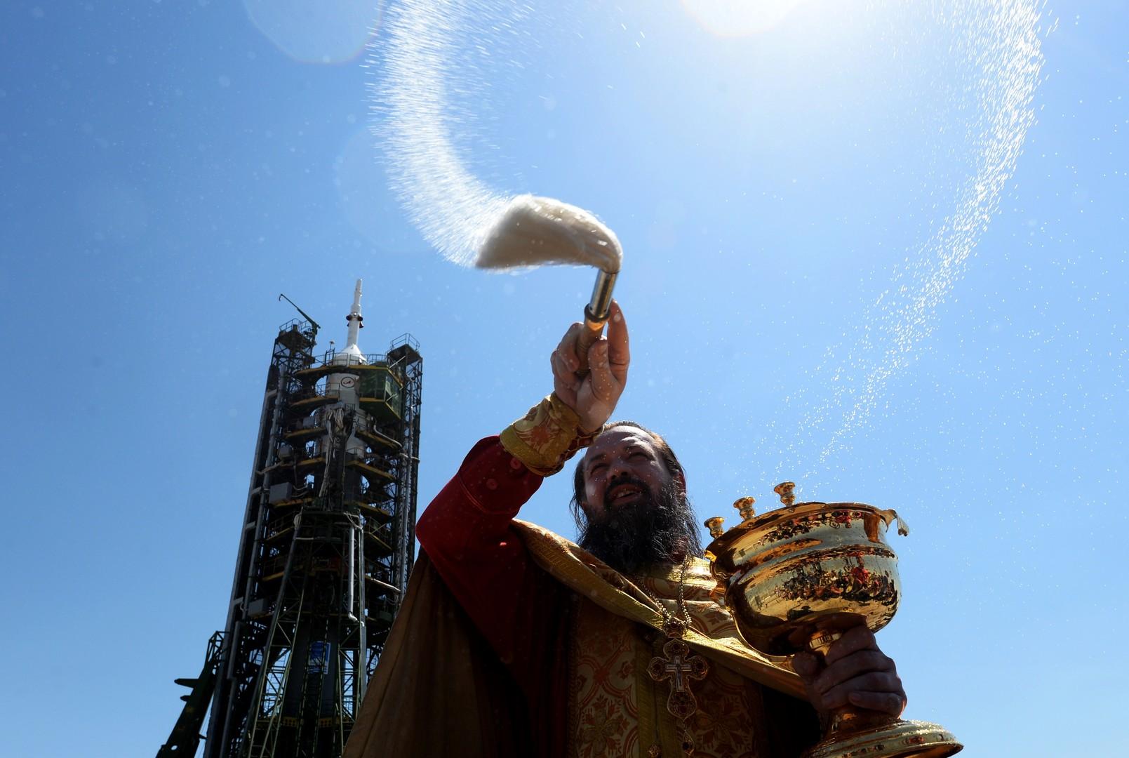 """Ein Priester bespritzt auf dem Weltraumbahnhof Baikonur eine """"Sojus-FG""""-Trägerrakete mit dem Raumtransporter """"Sojus TMA-13M"""" mit Weihwasser."""