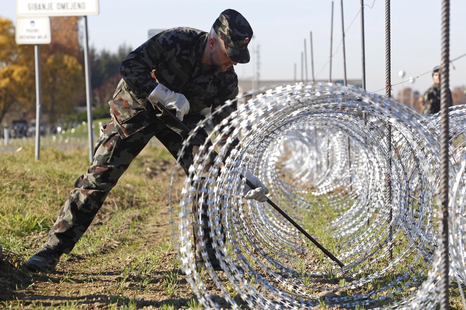 Ein slowenischer Soldat installiert Stacheldraht im Dorf Gibina an der Grenze zu Kroatien