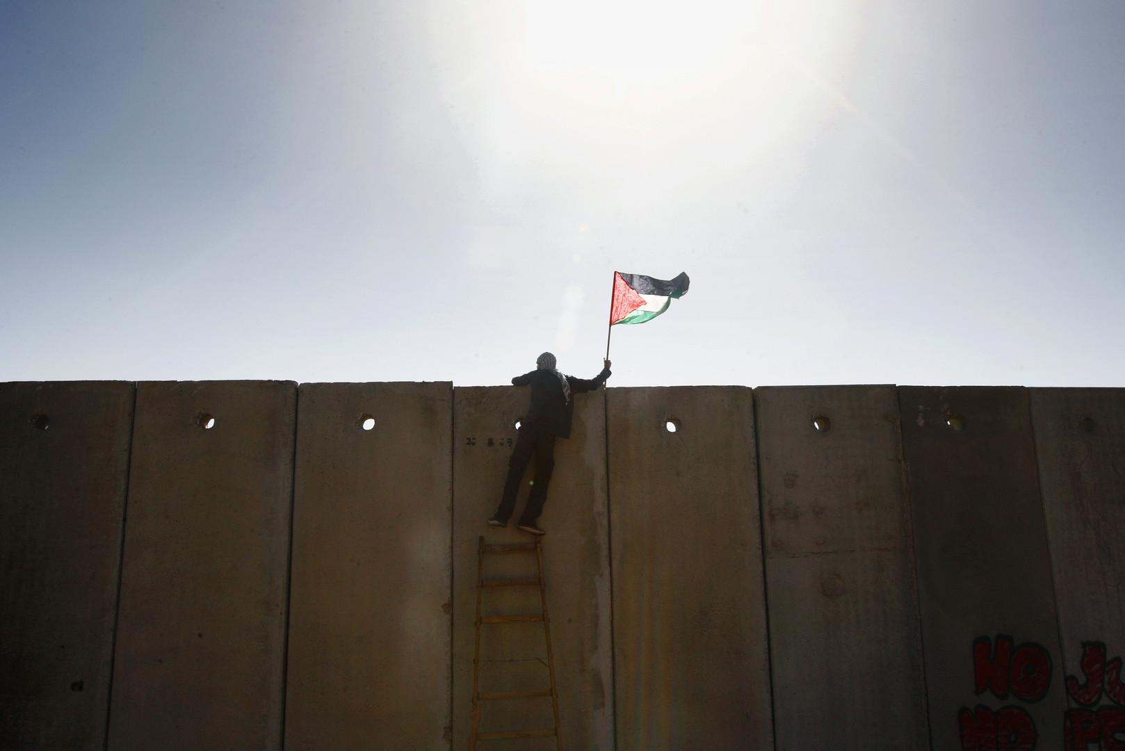 Ein palästinensischer Demonstrant besteigt den israelischen Schutzwall mit der palästinensischen Flagge in der Hand