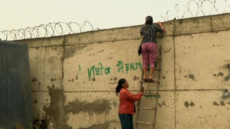 """Zwei Frauen klettern auf die """"Schandemauer"""", die die Slums und die Luxusviertel in der peruanischen Hauptstadt Lima trennt"""