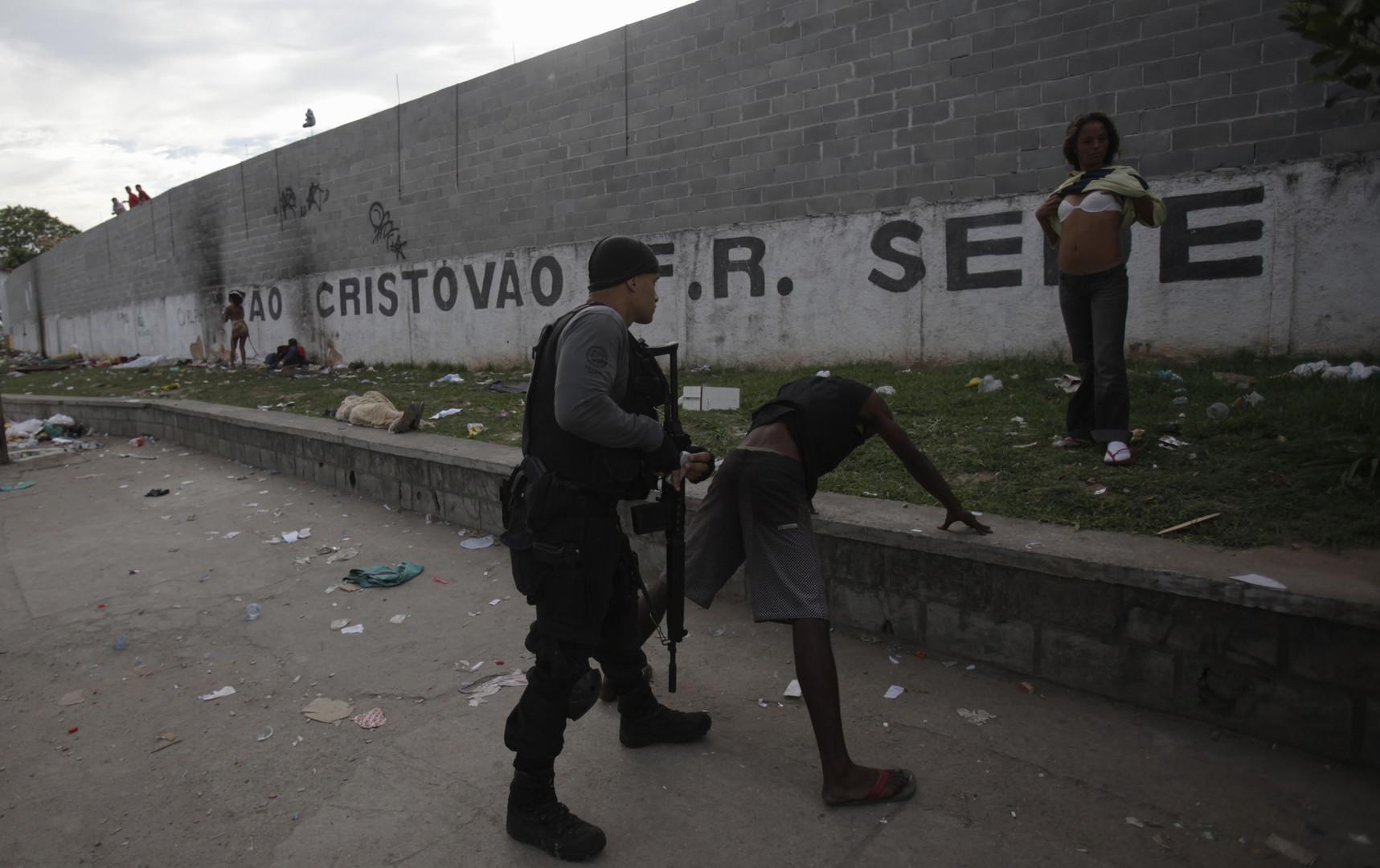 Ein Polizist durchsucht einen mutmaßlichen Crack-Süchtigen während einer Razzia in Rio de Janeiro. Im Hintergrund ist eine Mauer zu sehen, die das Elendsviertel Parque Uniao umgibt.