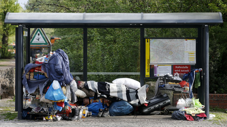 Ein Obdachloser schläft mit seinen wenigen Habseligkeiten in einer Bushaltestellte, Kreuzberg, Berlin; 8. April 2014
