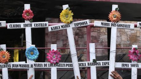 Menschen in Monterrey halten Kreuze mit den Namen der Opfer hoch, die während eines Überfalls des Zeta-Kartells getötet wurden. Mexiko, 25. August 2015.