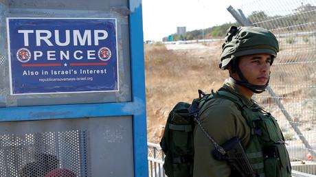 Ein israelischer Soldat steht vor einer Bushaltestelle mit Werbung der Kampagne von Donald Trump, in der Nähe der West Bank in der jüdischen Siedlung Ariel, Oktober 2016.