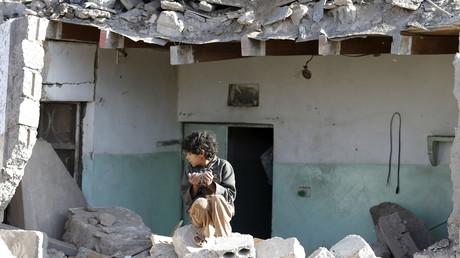 Ein Junge sitzt auf den Trümmern eines durch einen Angriff der saudi-arabischen Luftwaffe zerstörten Gebäudes. Sanaa, 26. März 2016