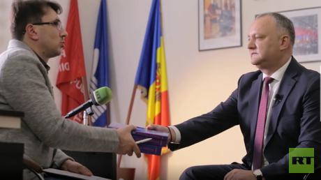 Der moldawische Präsident Igor Dodon überreicht sein Geschenk dem RT Deutsch-Redakteur Wladislaw Sankin: Die dreibändige Geschichte Moldawiens in russischer Sprache.