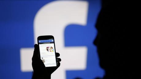 Ein Nutzer vor dem Hintergrund des Facebook-Logos