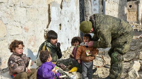 Russische Soldaten helfen Kindern in Aleppo