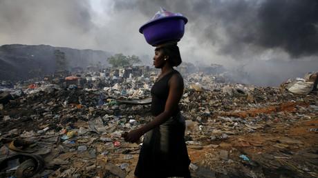 Eine Frau läuft über eine Mülldeponie in der nigerianischen Metropole Lagos.