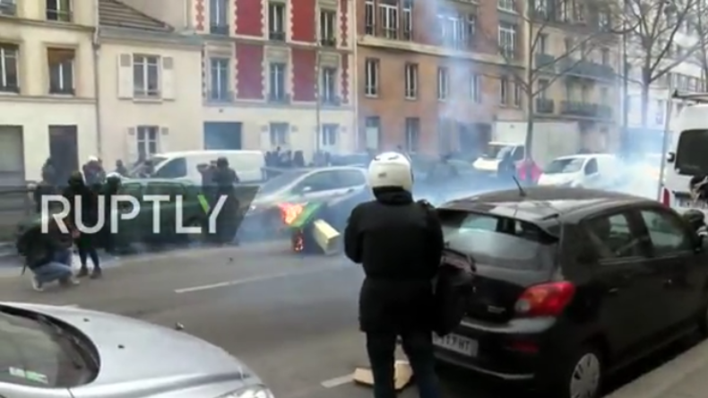 Das Bild zeigt Protestler in Paris, die Mülltonne in Brand gesetzt haben.