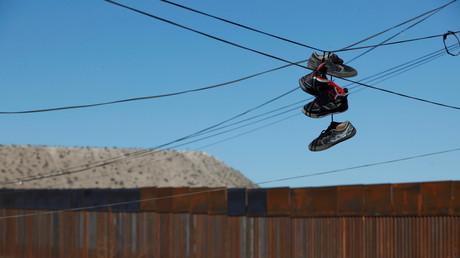 Schuhe hängen über Stromkabeln zwischen der amerikanisch-mexikanischen Grenze, in Ciudad Juarez, Mexiko.