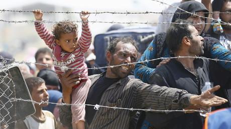 Ein syrischer Flüchtling wartet samt Kleinkind darauf, die syrisch-türkische Grenze passieren zu können.