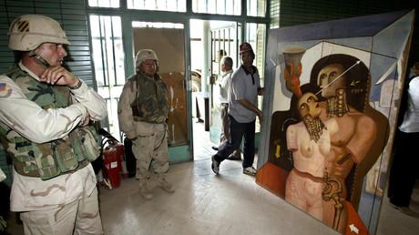 Ein US-Soldat sieht zu, wie Mitarbeiter des archäologischen Museums Bagdad wiedergefundene gestohlene Kunstschätze nach der US-Invasion zurück ins Museum tragen; 24. April 2003.
