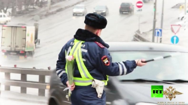 Russischer Verkehrs-Polizist winkt PKW-Fahrerin aus dem Verkehr.