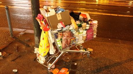 Ein Einkaufswagen, voll mit Plastikabfällen, steht verlassen auf der Friedrichstraße in Berlin.