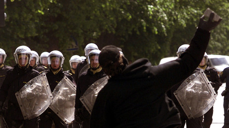 Ein maskierter Demonstrant attackiert die schwedische Polizei mit Steinen; Göteborg, 15. Juni 2011.