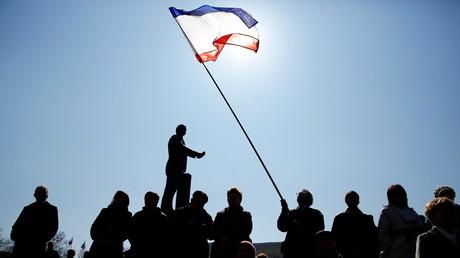 Die offizielle Krim-Flagge weht über die Demonstranten am 15. März 2014 in Simferopol. Auf dem Hintergrund ist Statue des Grunders der UdSSR Wladimir Lenin.