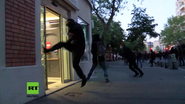 Vermummte Protestler schlagen Ladenfenster in Paris ein.
