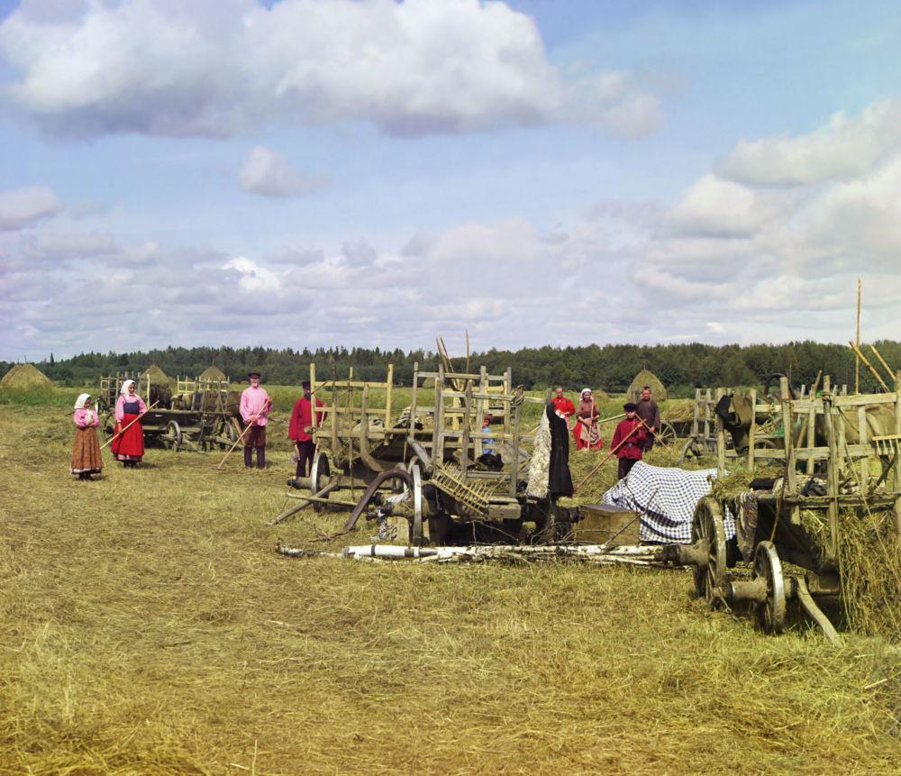 Landarbeiter stehen in der Nähe ihrer Ausrüstung und machen eine Pause vom Heu machen.