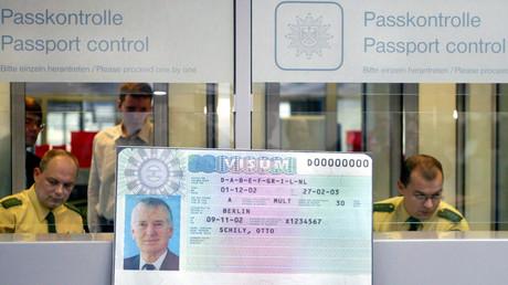 Zwei Grenzschutzbeamte hinter einem Beispielbild von einem EU-Visum, das ein Foto Otto Schilys ziert; 26. November 2002.