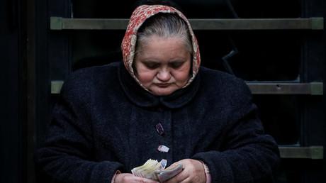 Eine ukrainische Rentnerin zählt das ihr zur Verfügung stehende Geld.