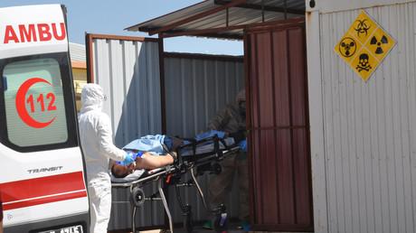 Türkische Sanitäter in Schutzanzügen  bringen einen Syrer aus Idlip zur medizinischen Behandlung.