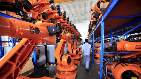 Ein Arbeiter passiert Regale mit Robotern aus zweiter Hand in einer Fabrik in Shanghai. Die chinesische