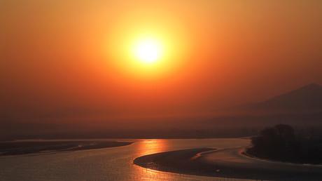 Die Sonnenaufgang über dem Yalu-Fluß nahe Sinuiju auf; Nordkorea, 1. April 2017.