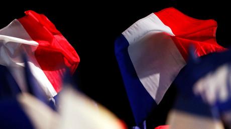 Anhänger schwingen die französische Flagge während einer Wahlkampfveranstaltung.