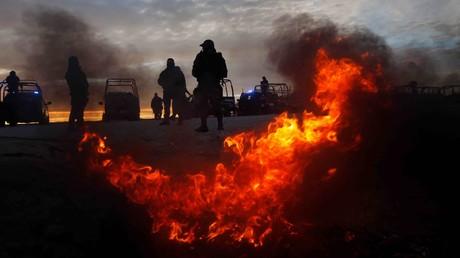 Beamte der mexikanischen Bundespolizei wärmen sich an einem Feuer an einer Straßenkontrolle in Ciudad Juarez, Mexiko 19. Januar 2017.
