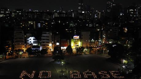 Demonstranten kreierten mit Kerzen einen Schriftzug aus Protest eines geplanten US-Stützpunkts in Japan, Tokio, Japan, 15. April 2010.