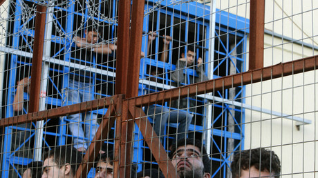 Symbolbild: Migranten lehnen am Zaun während eines Aufstandes im Pagani Flüchtlingslager auf Lesbos (2009)