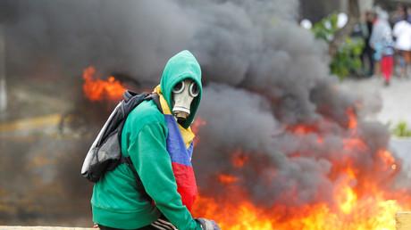 Ein Aktivist der Opposition vor einer brennenden Straßenbarrikade, Caracas, 24.  April 2017.