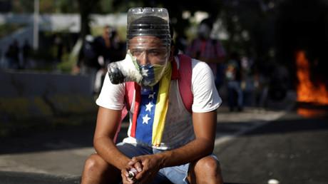 Ein Demonstrant mit einer selbst gebauten Gasmaske, maskiert mit einer venezolanischen Flagge auf einer Demonstration gegen Präsident Nicolas Maduro, Caracas, 24. April 2017.
