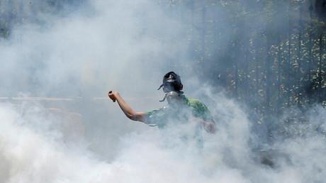 Ein palästinenischer Demonstrant im Tränengasnebel der israelischen Armee.