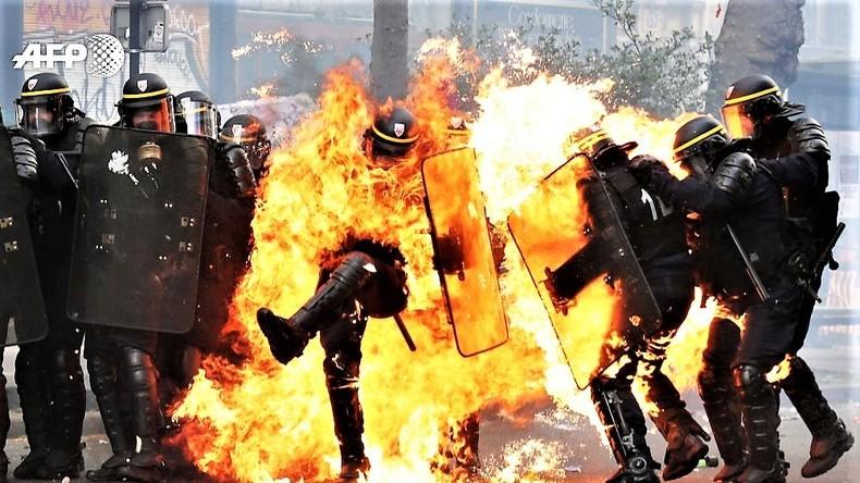 Ausschreitungen in Paris. Polizisten brennen und setzen Tränengas ein.