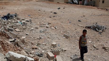 Ein Junge zwischen Fassbomben in der von Rebellen eingenommenen Stadt Deraa, Syrien, 1. Mai 2017.