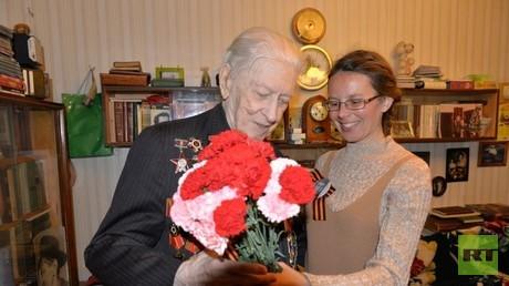 Kriegsveteran Michailowitsch Gwosdew erhält Nelken zum Tag des Sieges im Großen Vaterländischen Krieg.