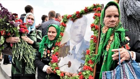 Die Kriegsteilnehmerinnen und Zwillingsschwestern Maria und Galina mit dem Porträt des Marschalls Georgi Schukow beim Marsch des Unsterblichen Regiments in Kiew am 9. Mai 2017. Georgi Schukow unterschrieb in der Nacht zum 9. Mai 1945 in Berlin-Karlhorst den Akt der Kapitulation.