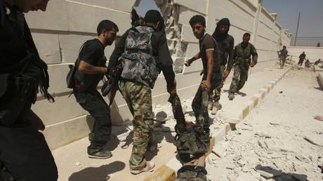 Symbolbild - FSA-Kämpfer schleifen die Leiche eines syrischen Regierungssoldaten während einer Offensive zur Eroberung von Aleppo durch einen Straßenzug; 26. August 2013.