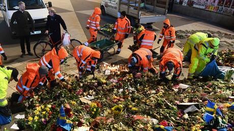 Helfer beseitigen Blumen, die nach dem Terrorattentat von Stockholm in der Einkaufsstraße
