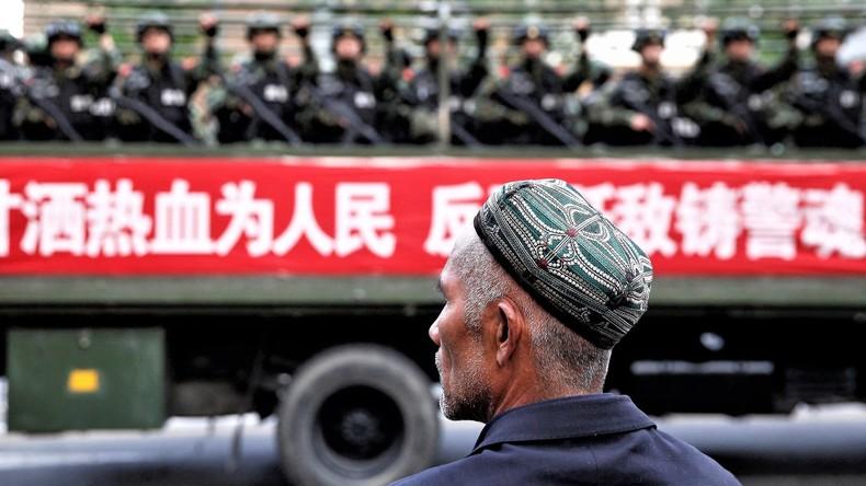 Ein Uigure , bewaffnete Polizisten in Xinjing, China