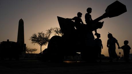 Silhouette von Kindern in Katar, die auf einer Kanone sitzen, welche das Fastenbrechen des Ramadans durch Kanonenschüsse einläutet, Doha, 27. Mai 2017.