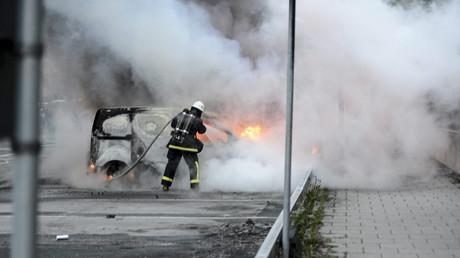 Ein Feuerwehrmann löscht brennende Autos im Stadtteil Rinkeby, Schweden, 23. Mai 2013.
