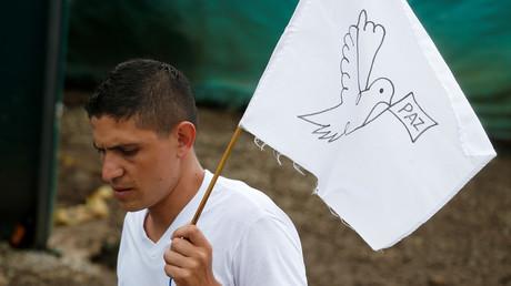 FARC-Rebell mit Friedensflagge während der jüngsten Waffenübergabe in Mesetas, Kolumbien, am 27. Juni.