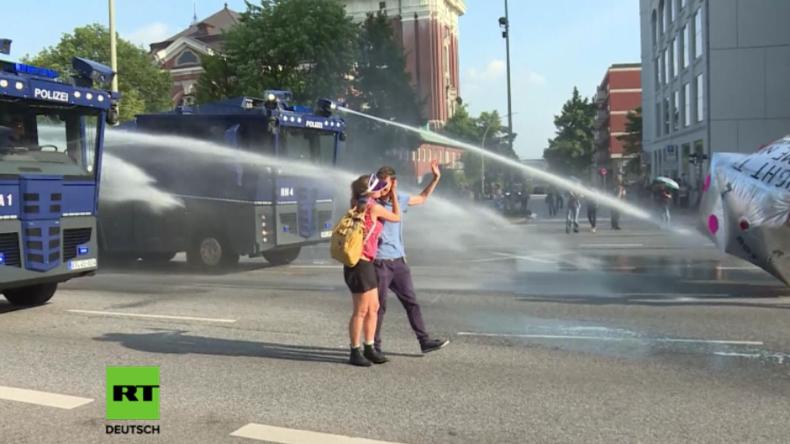 """Knutschen im """"Regen"""" – Protestler in bester Laune nutzen Polizei-Wasserwerfer als Sommerdusche"""