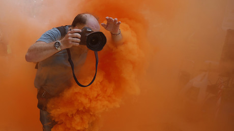 Ein Fotograf springt auf einer Demonstration von Feuerwehrleuten in Spanien über eine Gas-Kartusche; Sevilla, 29. September 2012.