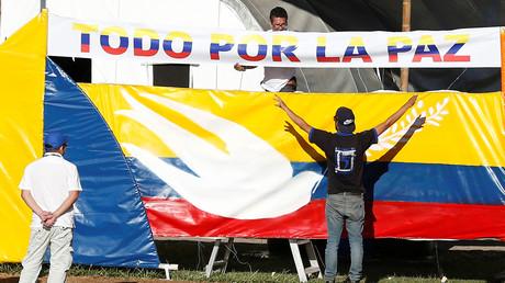 Ein Mann hängt ein Banner mit dem Text