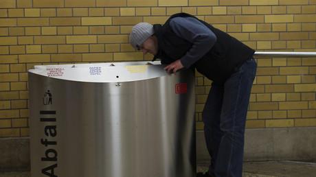 Ein Mann sucht im Abfalleimer nach Verwertbarem